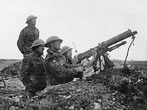 Vickers machine-gun crew, Western Front, during World War I. A machine-gun crew using a Vickers machine-gun to fire at an aircraft. The Number 1 of the crew is clearly looking through the sights on the back of the gun barrel as he fires. The Number 2 is feeding in the ammunition belt. The other two would have been needed to help carry the gun and its ammunition.