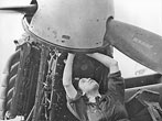 WAAF Checks Mosquito Engine. Among technical duties carried out by members of the British Women's Auxiliary Air Force, are those in the electrical and mechanical branches. Airwomen at a large aircraft repair depot of R.A.F. Maintenance Command are adapting Canadian made Mosquito fighter bombers for use in the Far East.