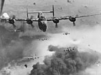 Through flak and over the destruction created by preceding waves of bombers, these 15th Air Force B-24s leave Ploesti, Rumania, after one of the long series of attacks against the No. 1 oil target in Europe.