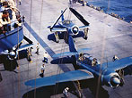 Helldiver Planes on Carrier Deck: Two Navy Helldiver planes on the deck of an aircraft carrier, one with wings extended, one with wings folded. (Bettmann/CORBIS)