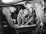USS Antietam (CV-36) - De-Briefing Session - After returning from strikes on enemy targets in the Wonsan area, these three Navy pilots on the aircraft carrier USS Antietam go into a de-briefing session, and check themselves on targets hit and damaged. Left to right: Ens. Robert L. Thomas, ... Lt(jg) Robert F. Baker ... and Ens. Howard E. Foabn.