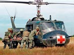 A wounded member of the 1st Plt. Company-C 25th Infantry Division, is helped to a waiting UH-1D Iroquois helicopter in Vietnam, May 10, 1967, during the Vietnam War. (AP Photo)