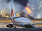 A Boeing 737 passenger plane sits on the tarmac of Rafik Hariri International Airport, in Beirut, Lebanon, Friday, July 14, 2006, while fuel storage tanks burn after Israeli helicopter gun ships targeted it with missiles late Thursday. Israeli air raids on suburbs of the Lebanese capital, where Hezbollah has its strongholds.